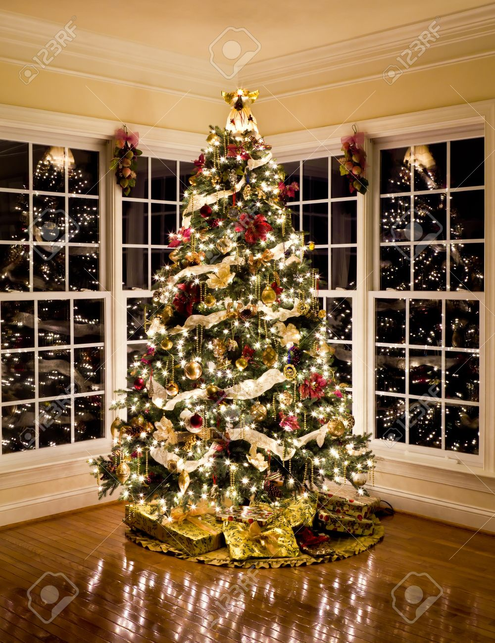 Christmas tree with presents and lights - Christmas Tree With Presents And Lights Reflecting In Windows Around The Tree In Modern Home Stock