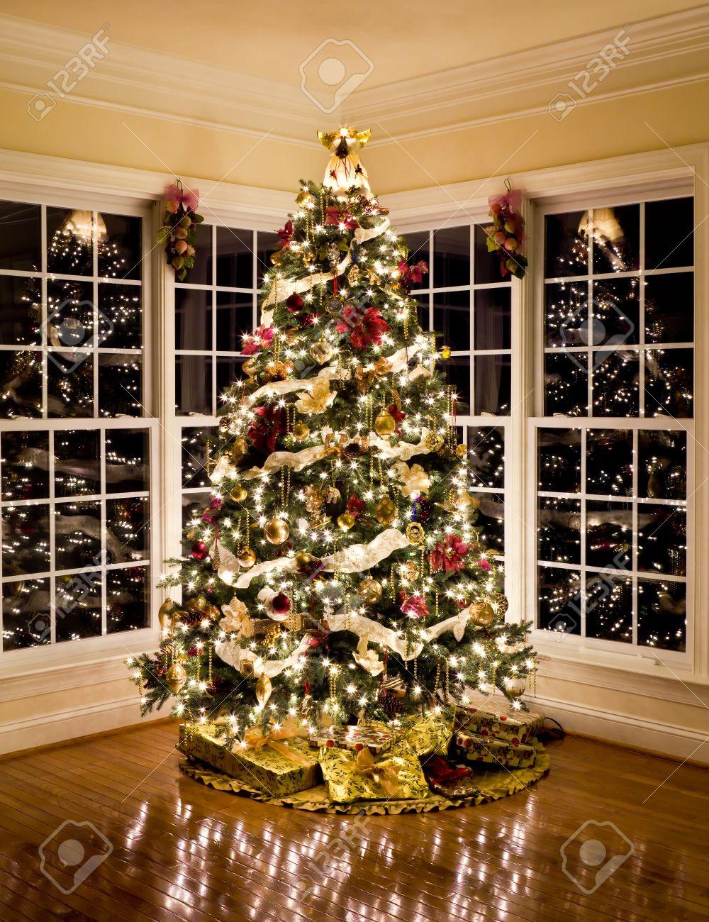 foto de archivo rbol de navidad con regalos y luces que refleja en ventanas alrededor del rbol en el hogar moderno