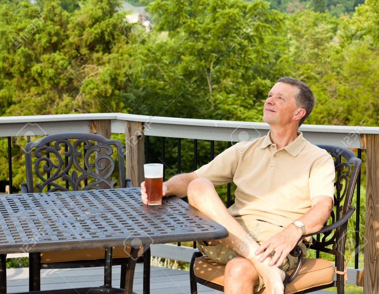 Moyen homme âgé assis sur la table de jardin en fonte d\'aluminium sur le  pont et en buvant un verre de bière dans le jardin