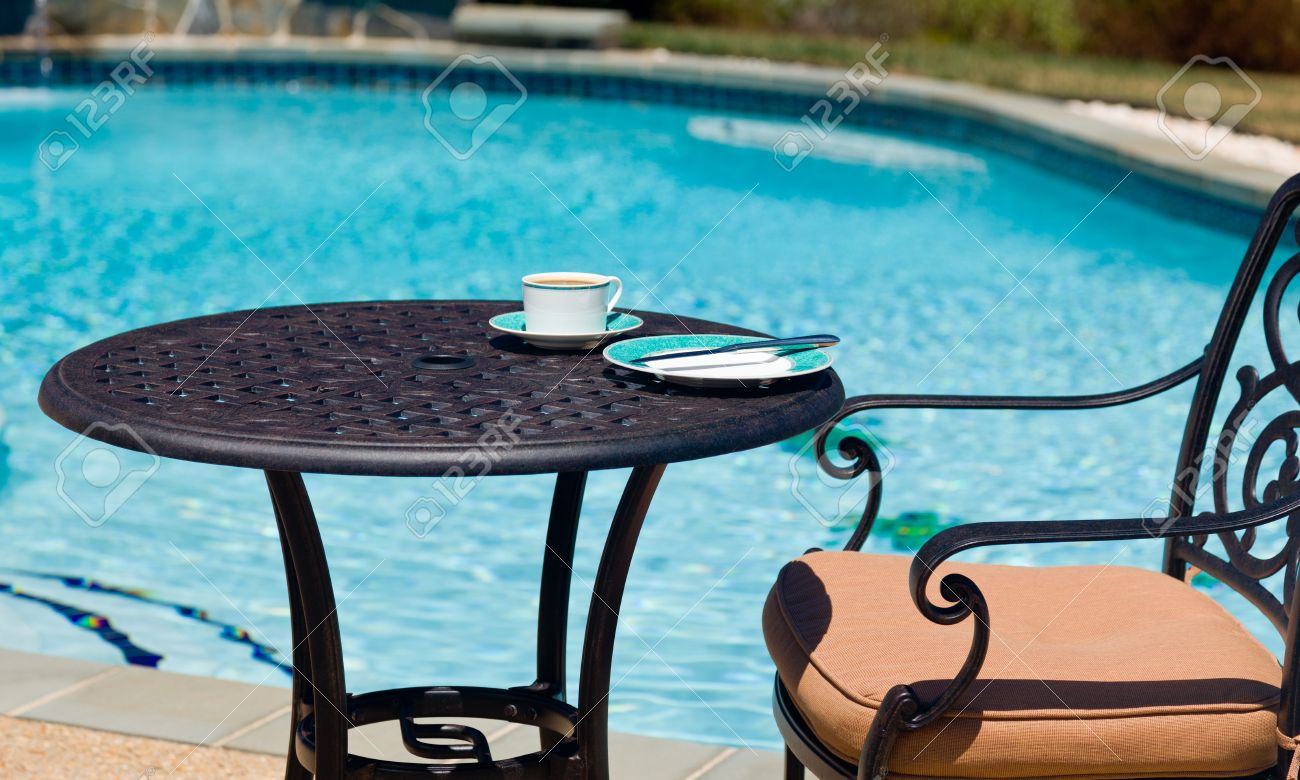 Coffee And Plate On Cast Aluminum Table And Single Chair By The Side Of Swimming  Pool