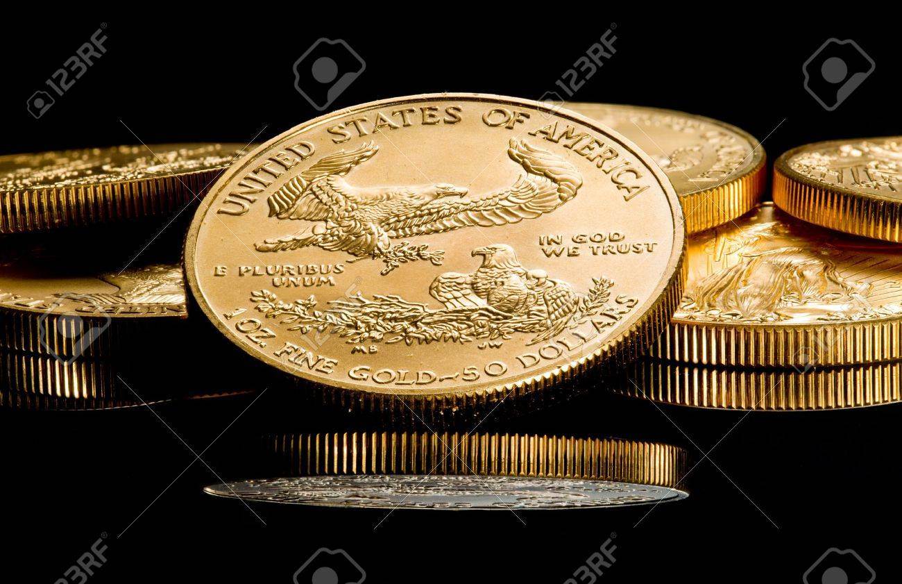 Close up of a solid gold eagle one ounce coin stacked on other coins and reflected in black surface Stock Photo - 10085714