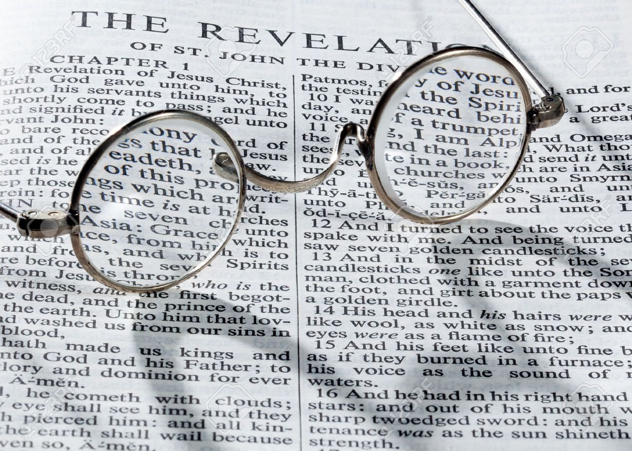 old fashioned round reading glasses laying on a page from the