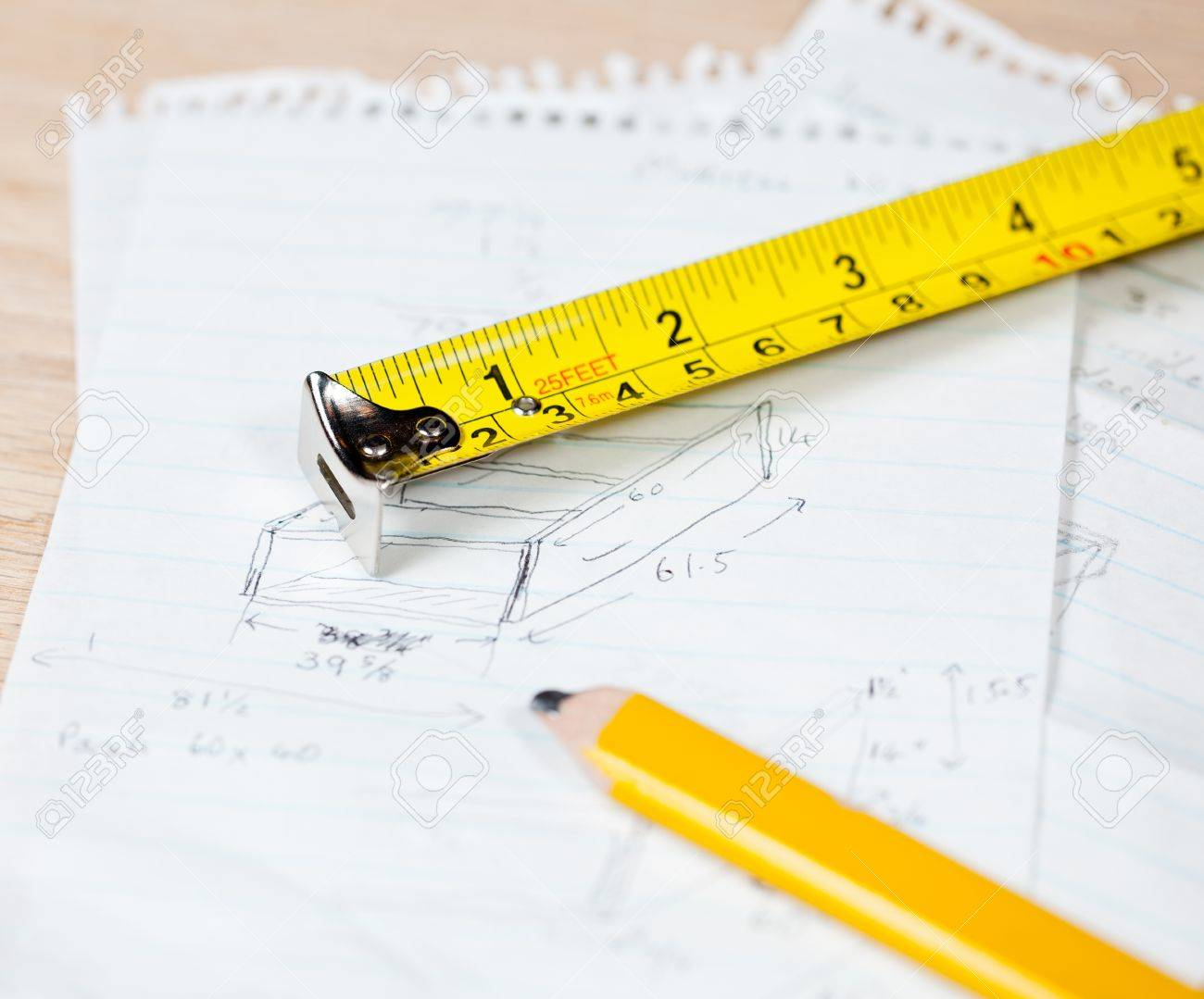 Tape measure and pencil laying on plans for a woodworking project Stock Photo - 11526623