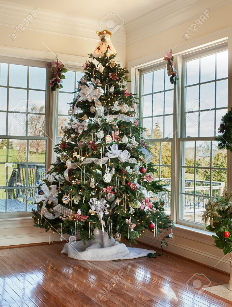 Christmas tree decorated with silver and white ribbons and ornaments in family home Stock Photo - 11526714