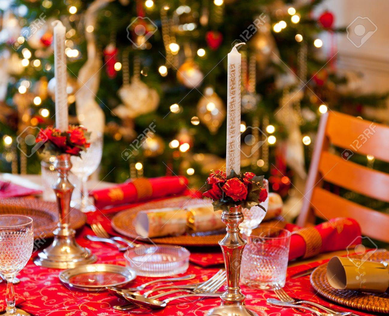 Christmas crackers on table set for Christmas lunch with candles and tree  in background Stock Photo