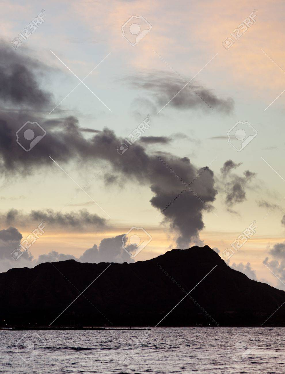 Clouds appear to be smoke from volcano of Diamond Head at sunrise in Hawaii Stock Photo - 12451430