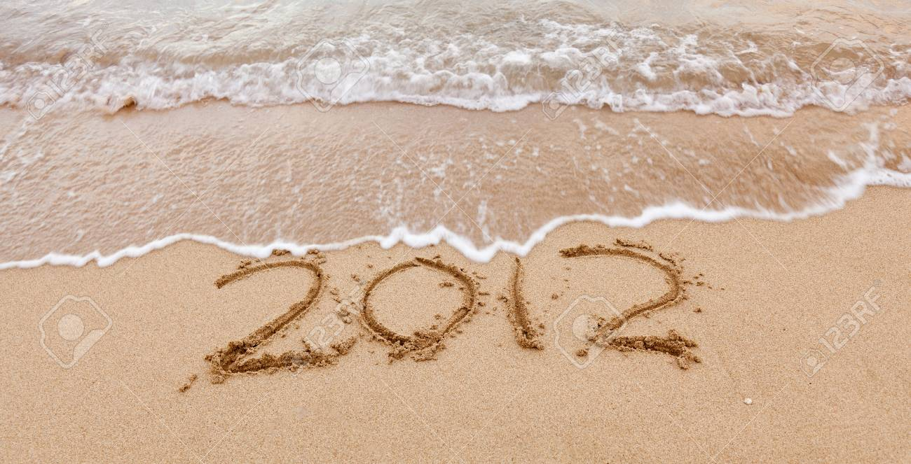 2012 written in sand on beach with sea waves starting to erase the word Stock Photo - 12451518