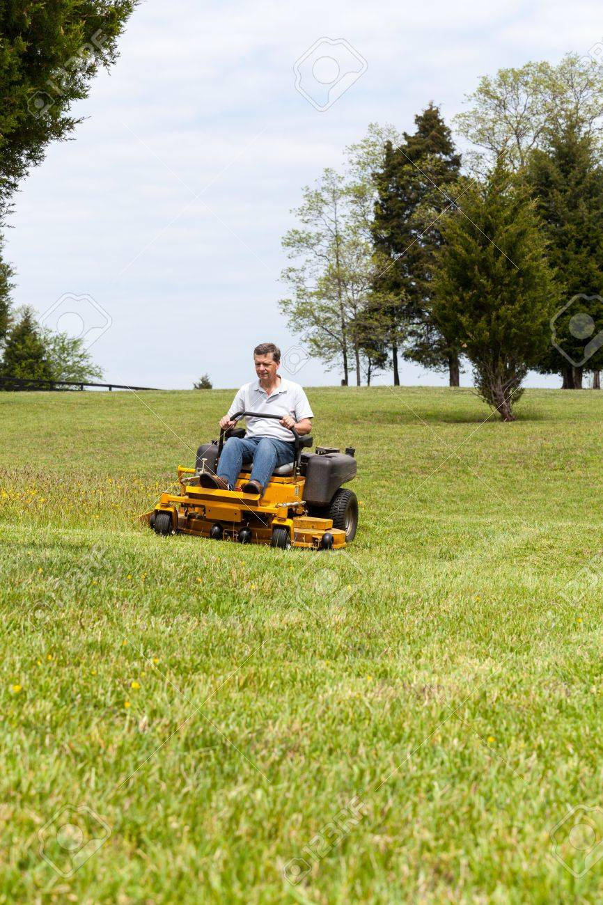 Senior Retired Male Cutting The Grass On Expansive Lawn Using