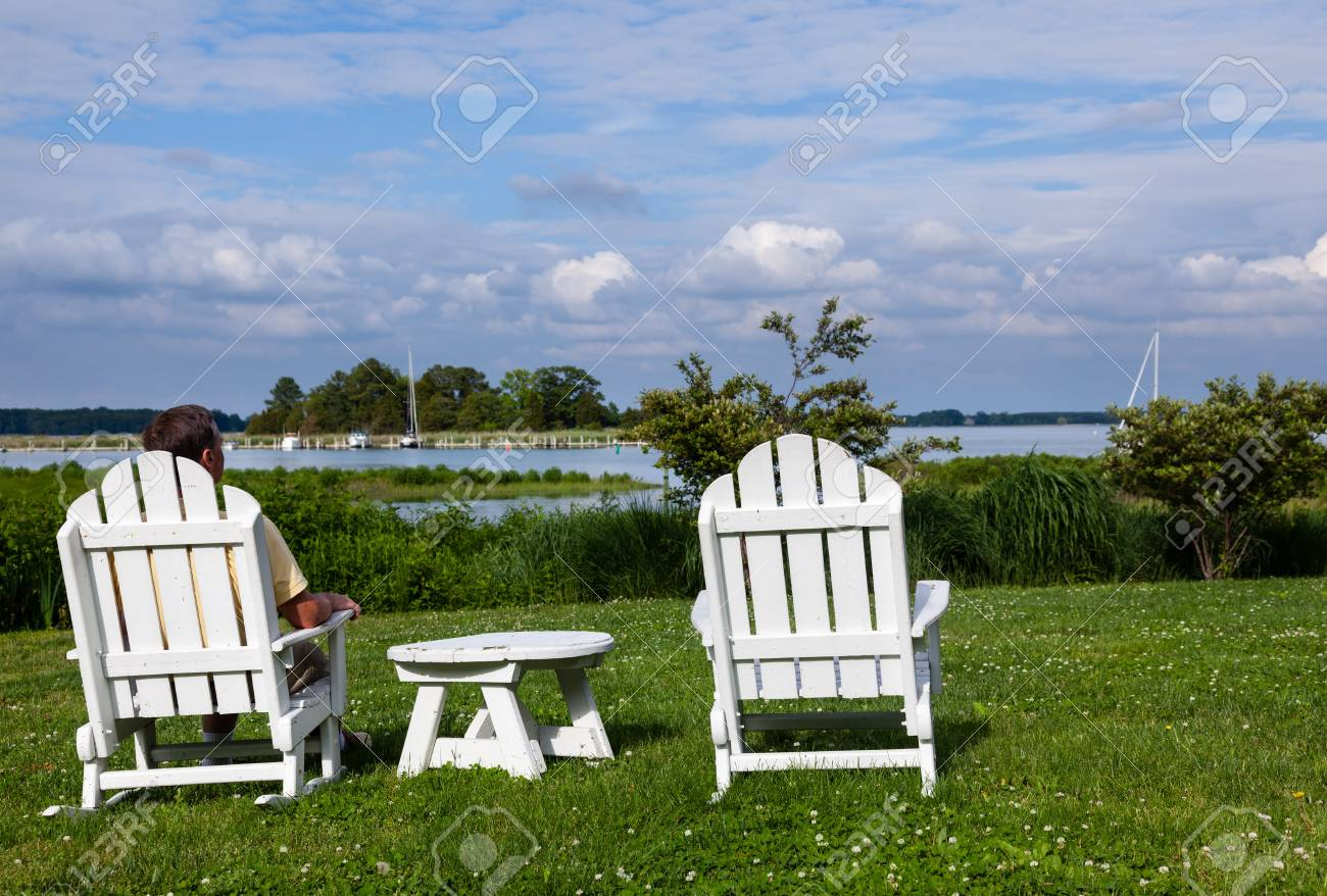Patio chairs by side of the Chesapeake bay overlooking St Michaels harbor with senior male Stock Photo - 13858860