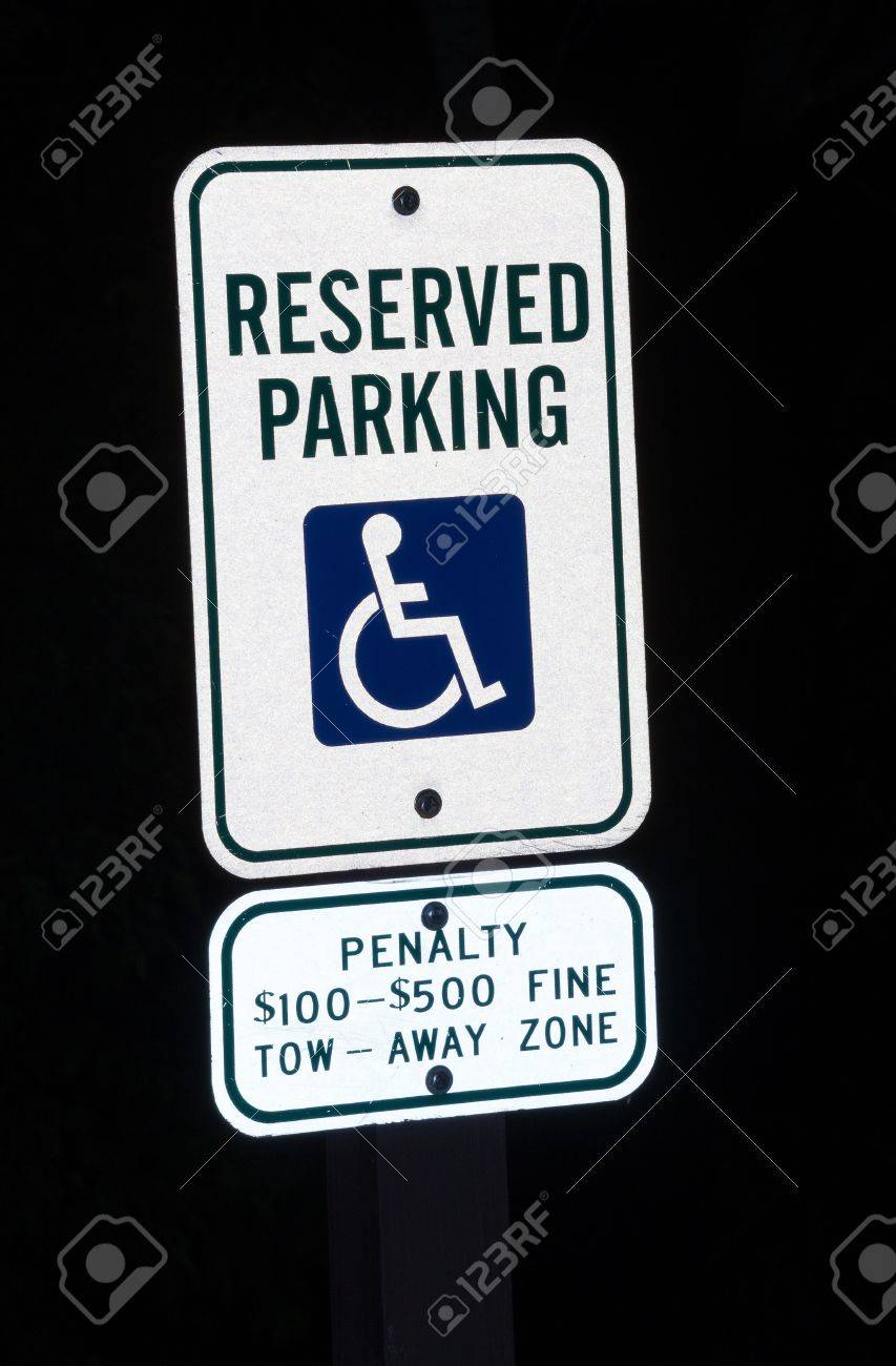Image Of A Disabled Parking Sign At Night With Penalty For Misuse ...