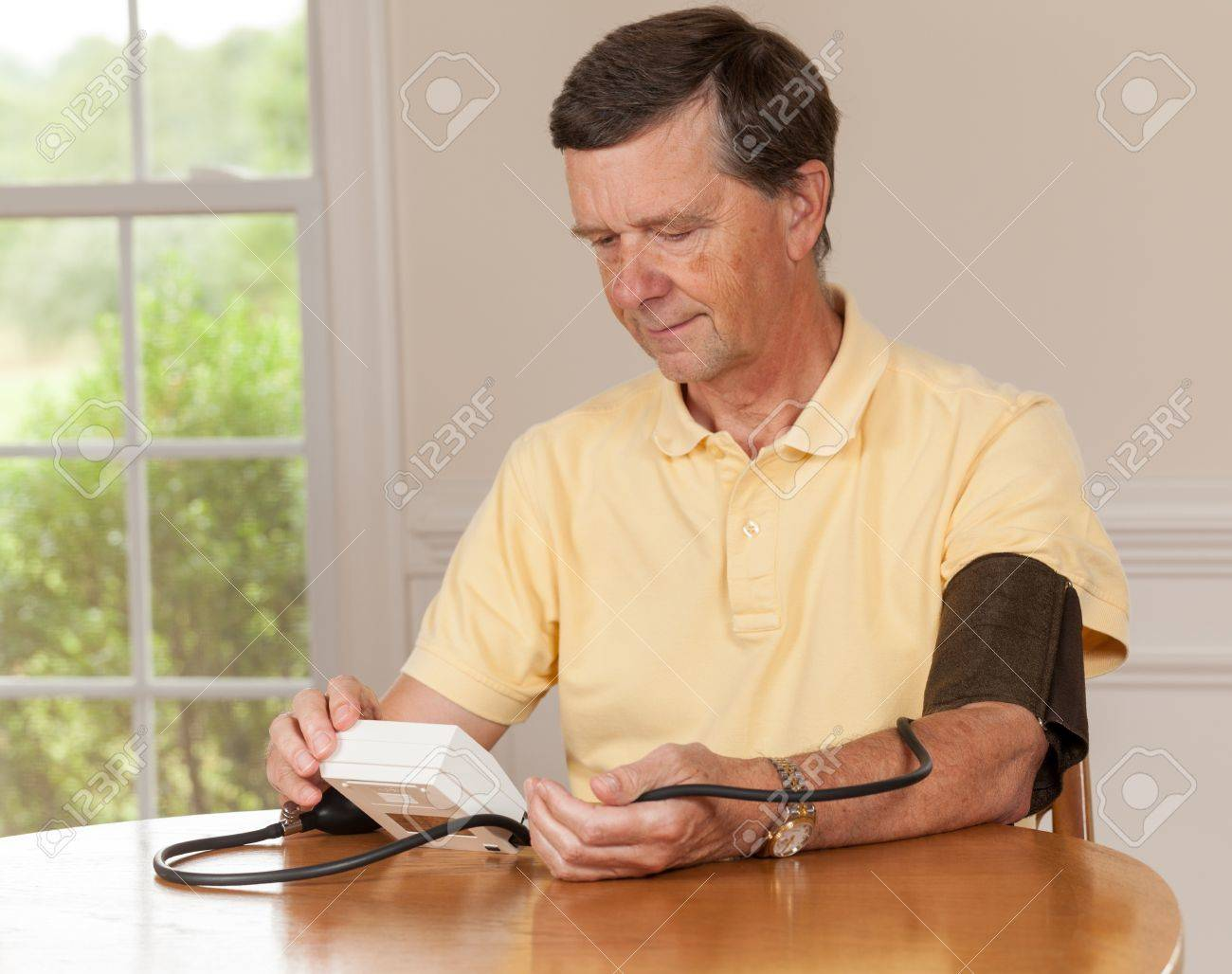 Senior caucasian retired male taking blood pressure at home Stock Photo - 14443215