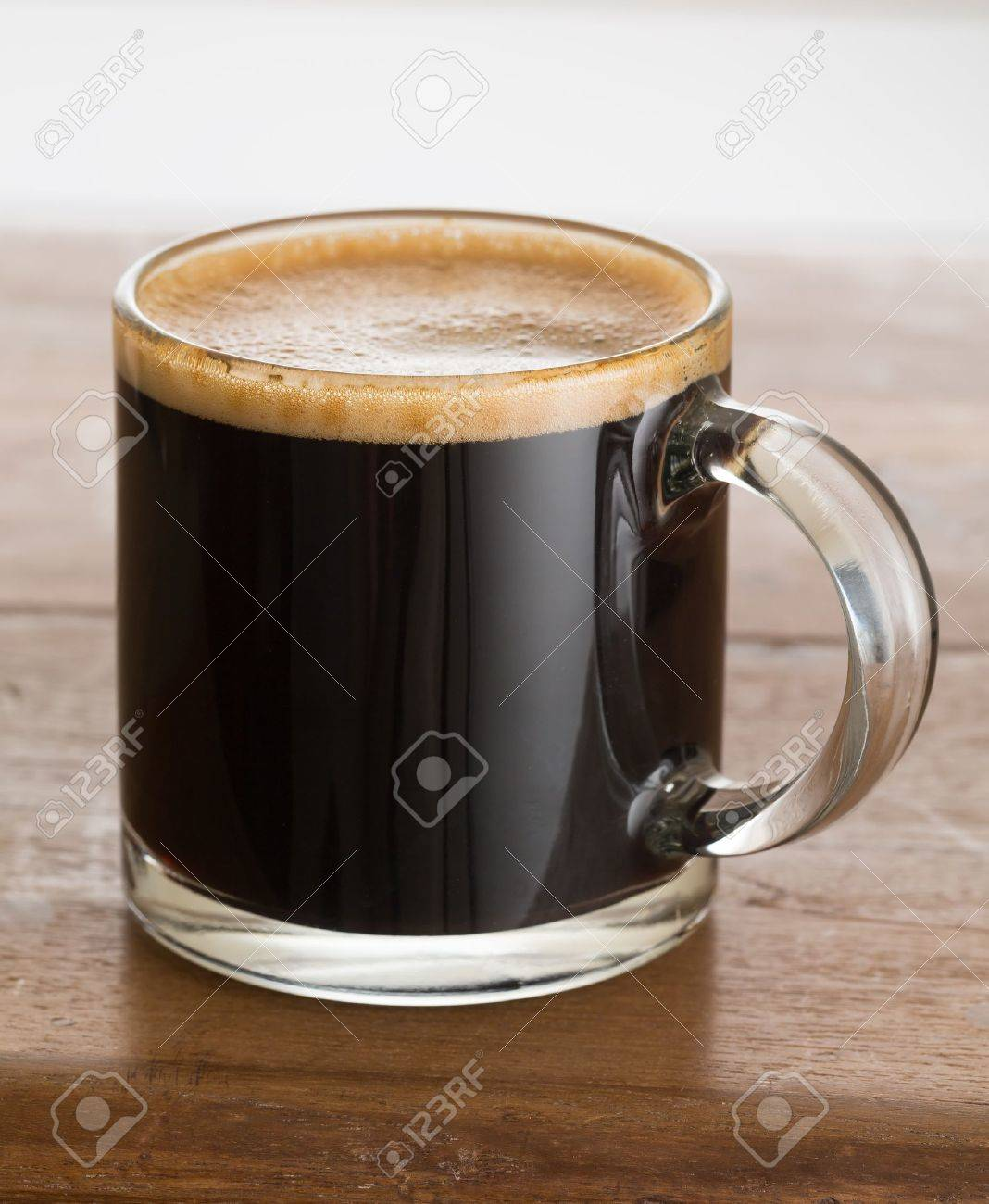 black expresso coffee in small glass cup on wooden table stock