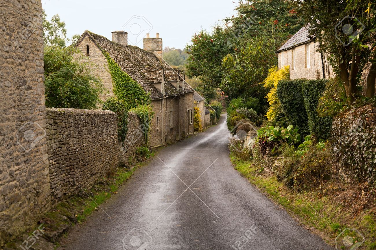 Narrow lane in vilalge of Minster Lovell in Cotswolds with stone cottages - 16449564