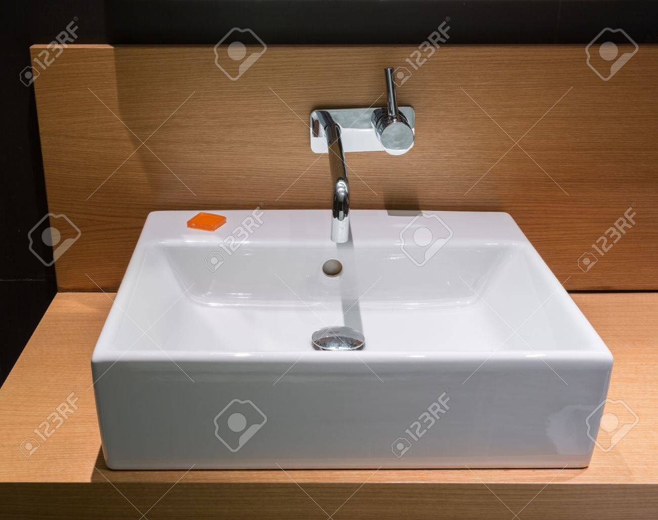 Details of modern square ceramic sink and faucet tap in surface mount on wooden surface Stock Photo - 18152548