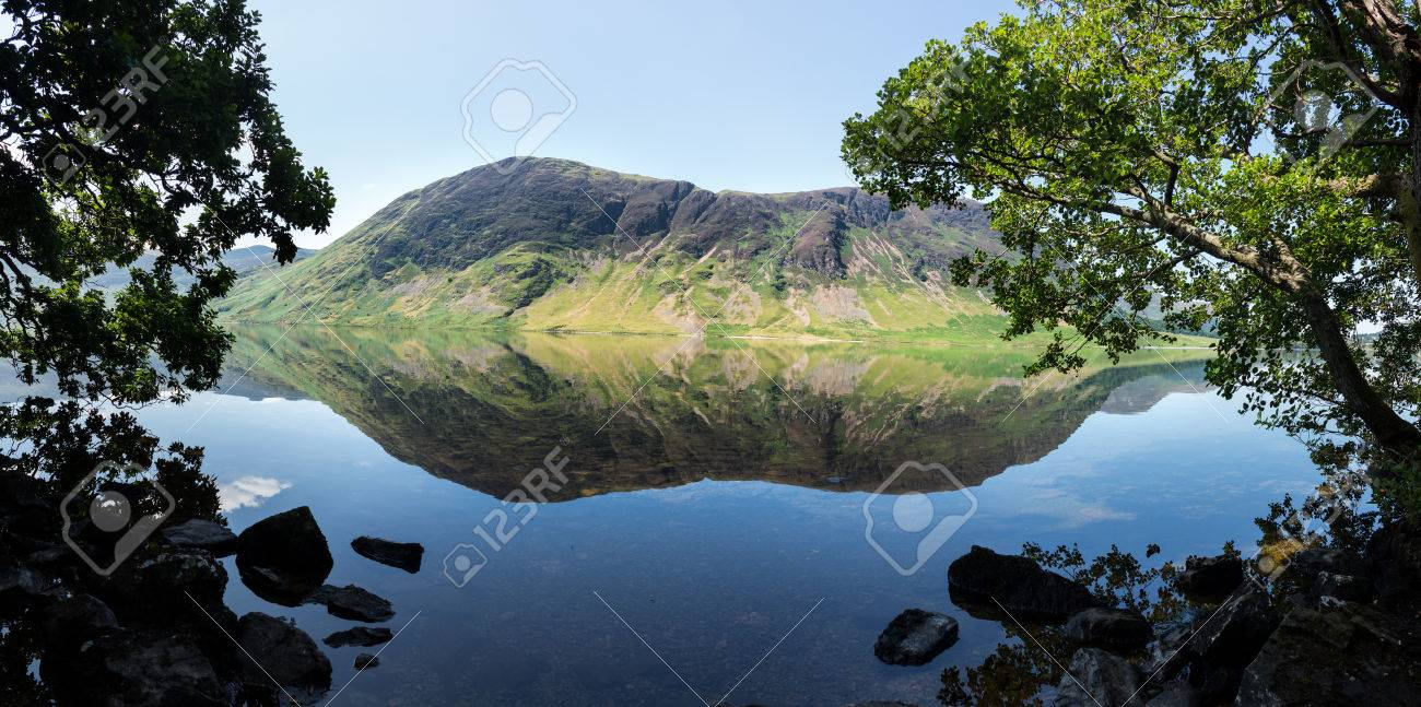 Mirror like reflection of the Lake District hills surrounding Crummock Water framed by the trees on the lakeside. Idyllic image from the English Lakes Stock Photo - 23730761