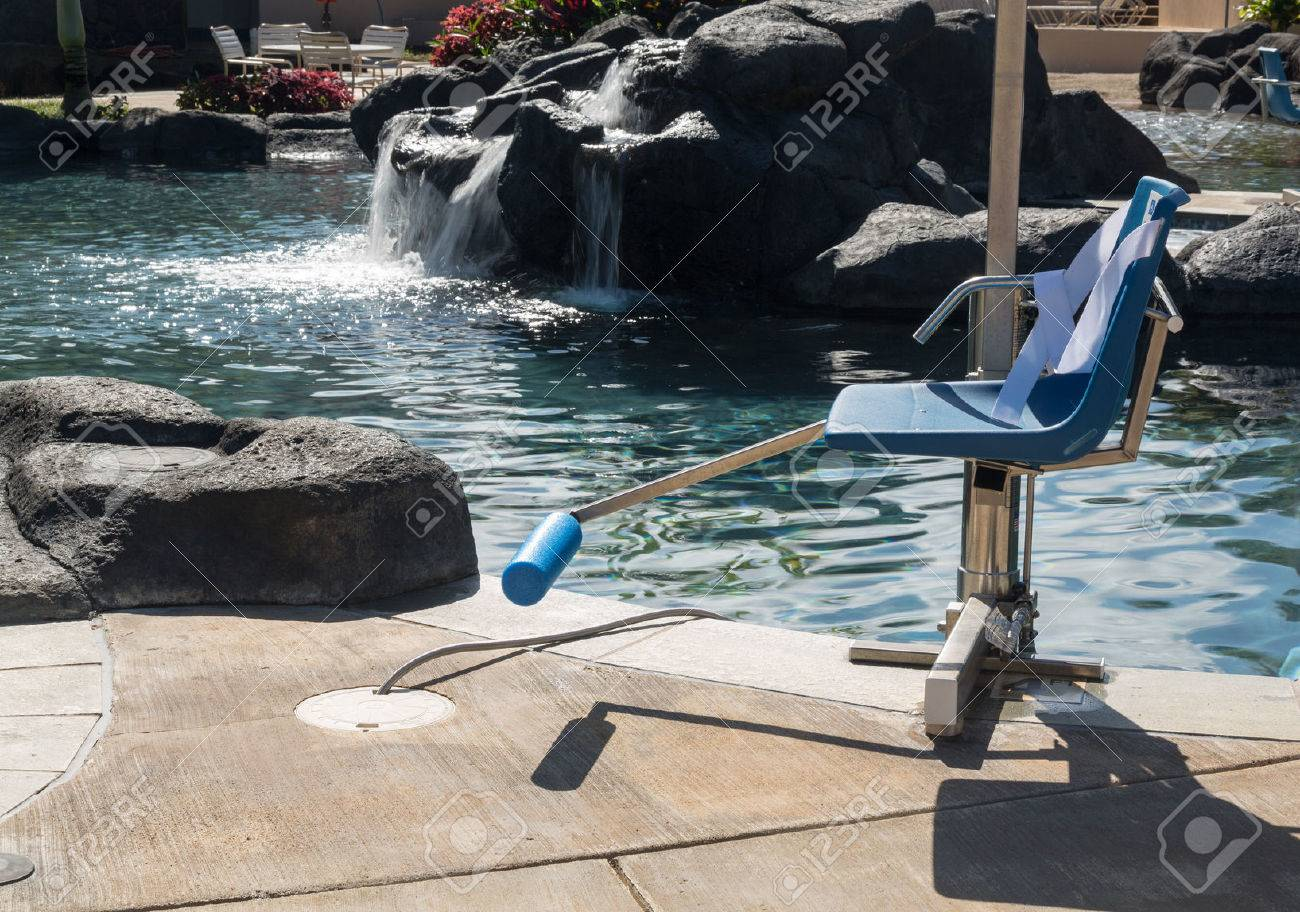 chair lift for disabled person to enter resort swimming pool stock