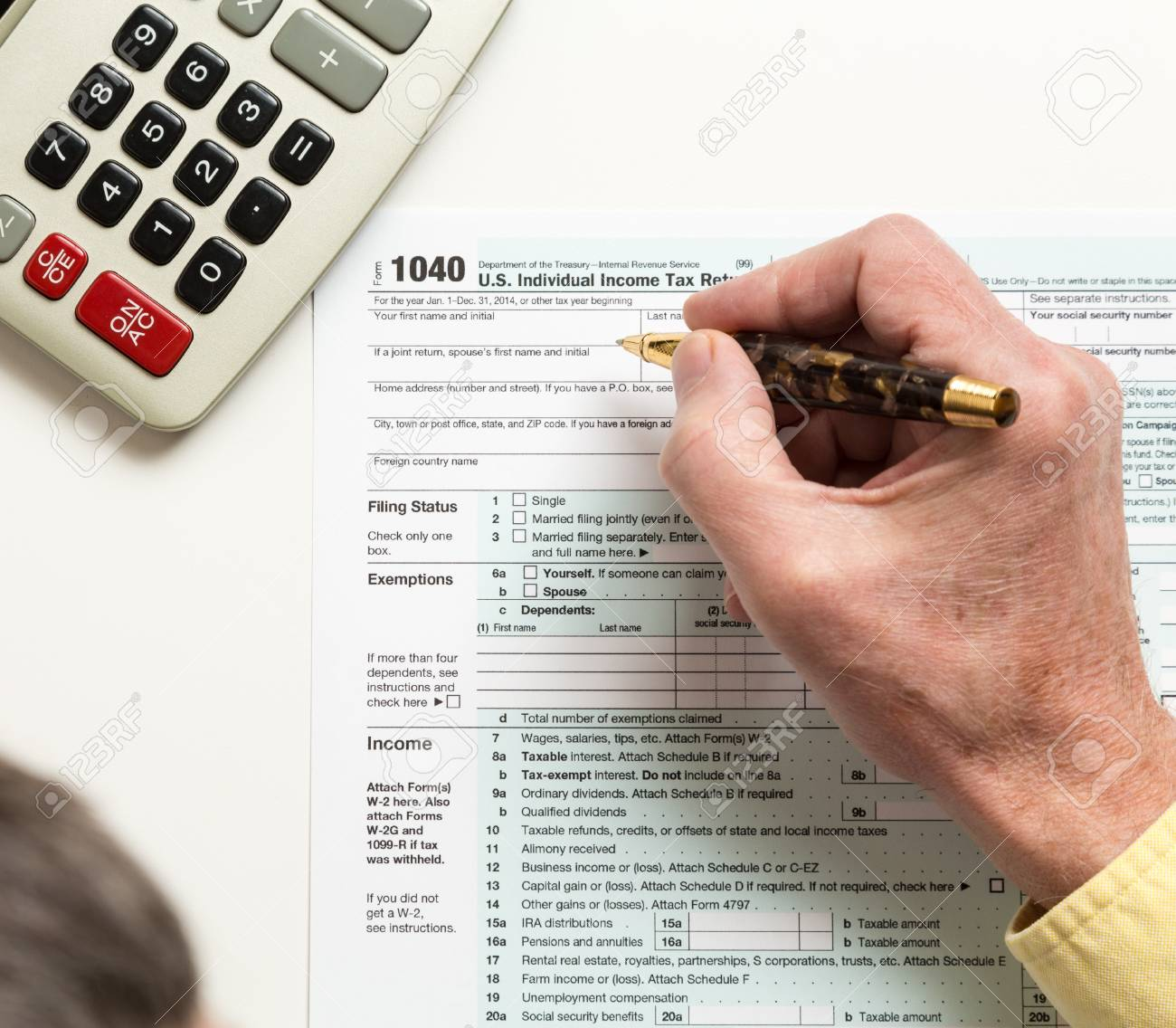 Male caucasian hand holding pen above USA tax form 1040 for year