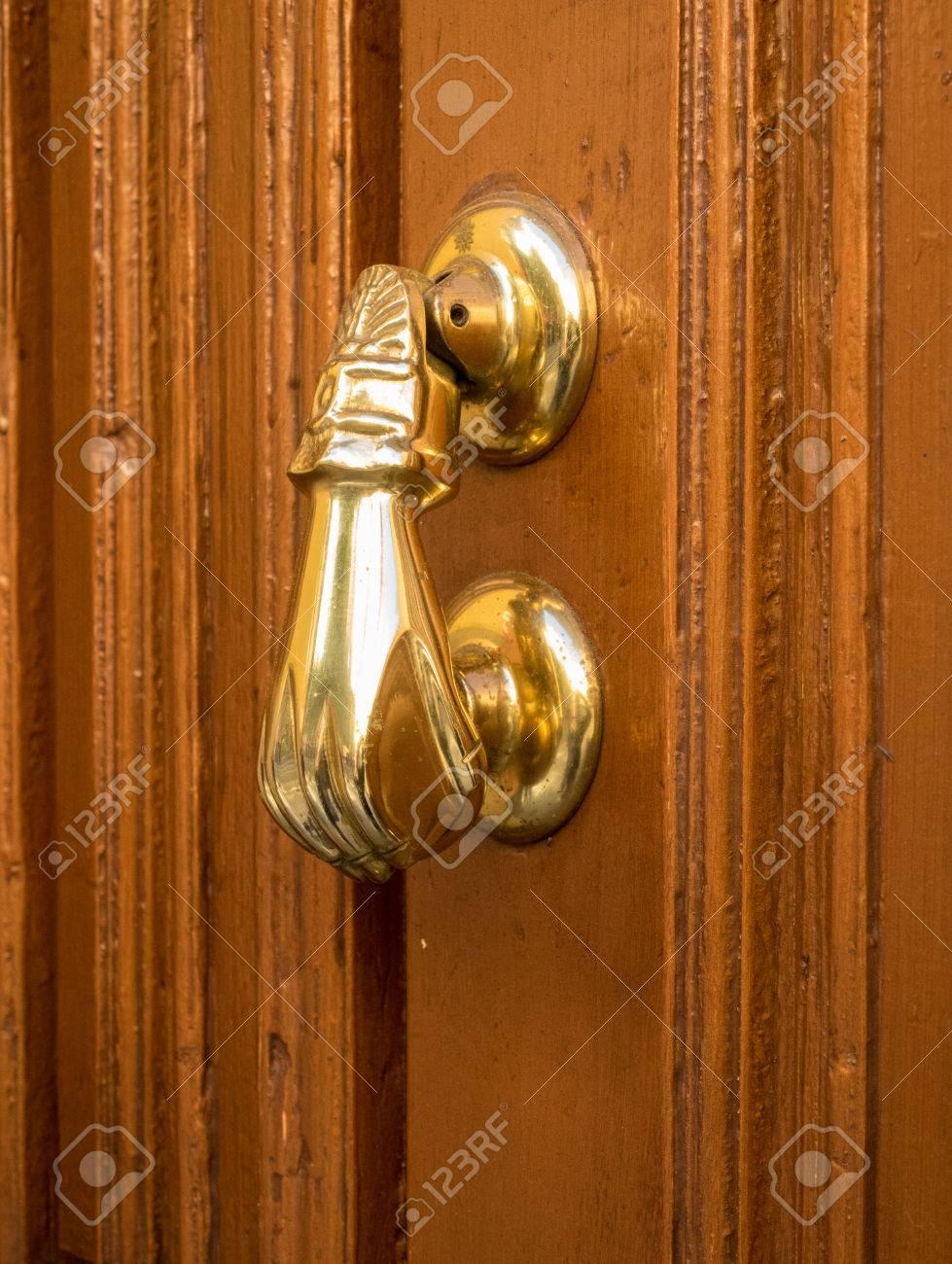 brass door knocker. side view of brass door knocker shaped like a hand on old wooden stock photo