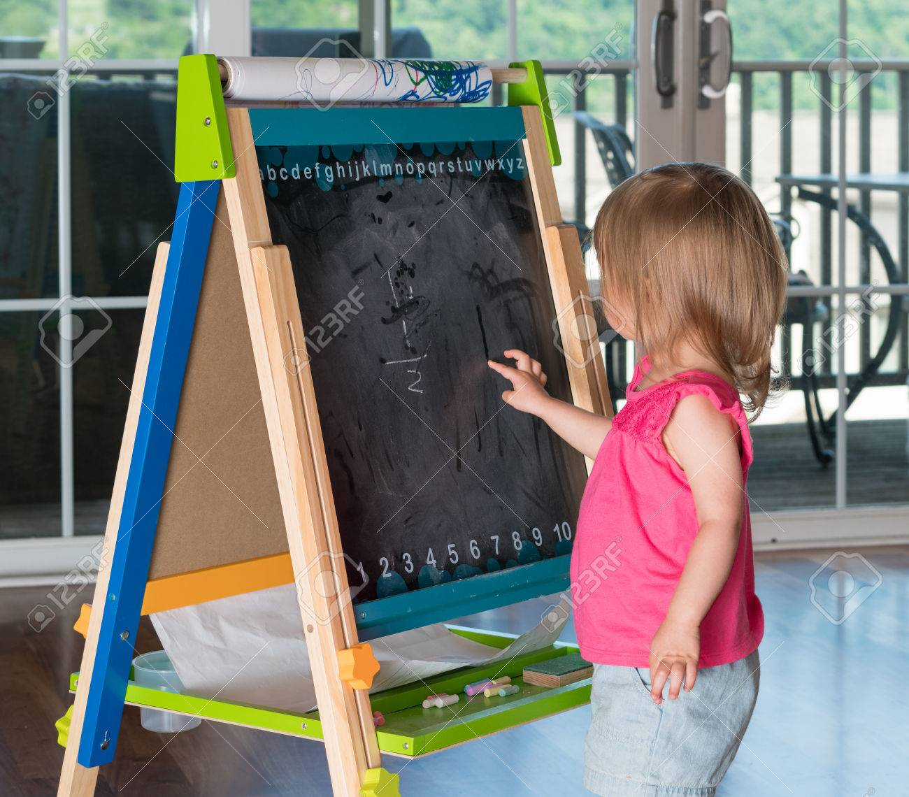 young two year old girl drawing with finger on blackboard on stock