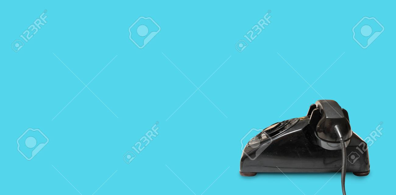 Side view of old and antique rotary telephone on blue background