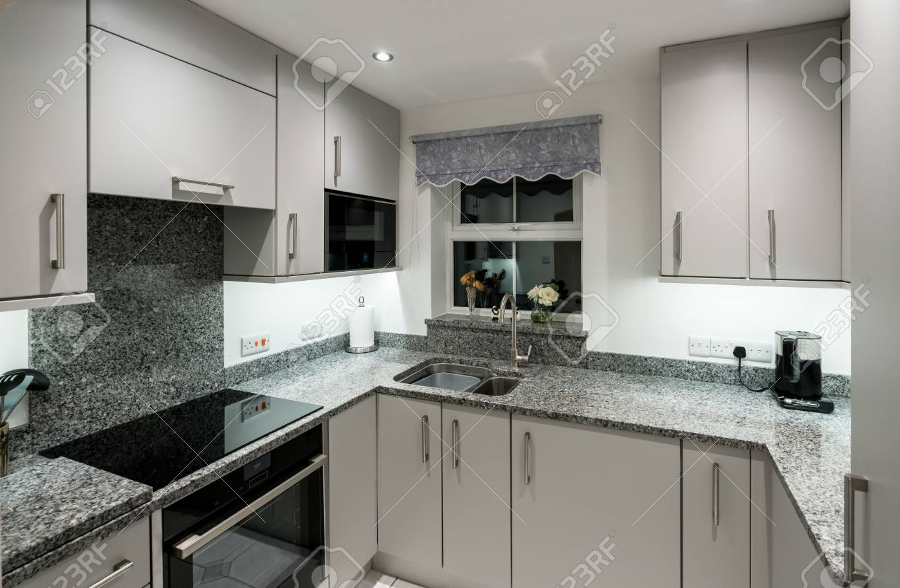 Small modern kitchen in UK apartment with granite and new appliances..