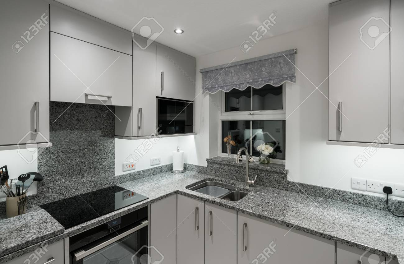 https://previews.123rf.com/images/backyardproduction/backyardproduction1712/backyardproduction171200031/92309681-small-modern-kitchen-in-uk-apartment-with-granite-and-new-appliances-including-induction-cooktop.jpg