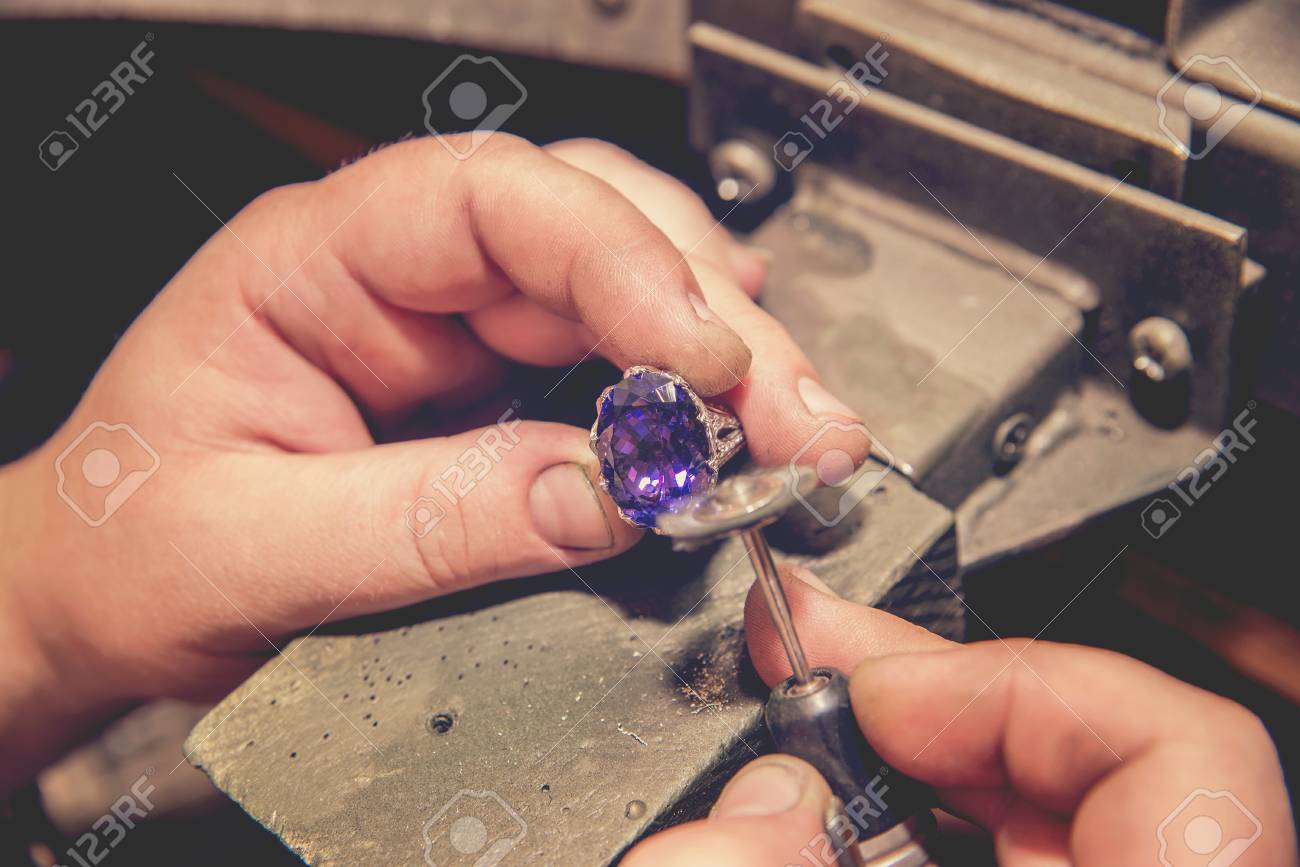 Master jeweler produces a gold ring with a big blue stone - 109386773
