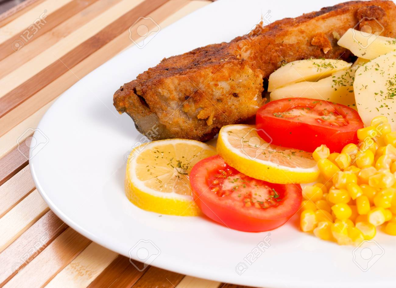 Fried carp and vegetables on the plate Stock Photo - 17203030