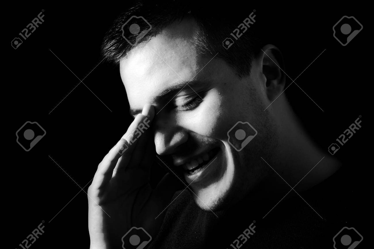 Close up of young smiling man in low key black and white stock photo