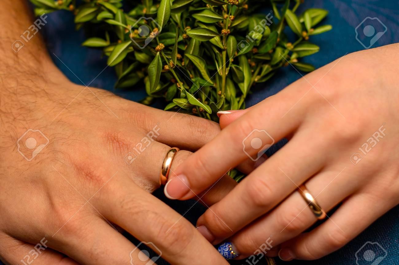 Foto Von Zwei Handen Mit Schonen Hochzeitsringen Und Grunblattern