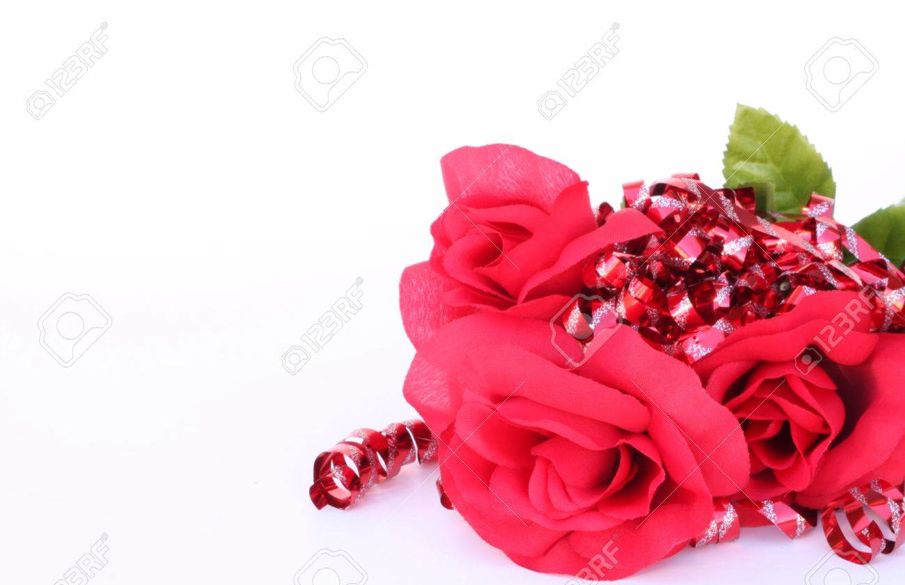 red roses surrounded by red ribbons with silver sparkles on a