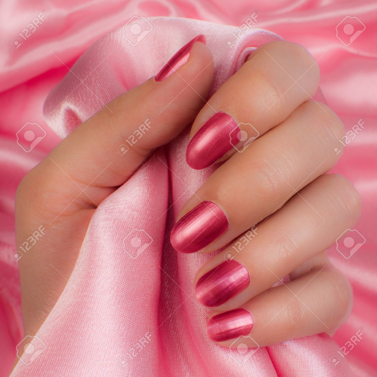 Female Hand With Pink Nails Holds Pink Satin On Pink Background ...