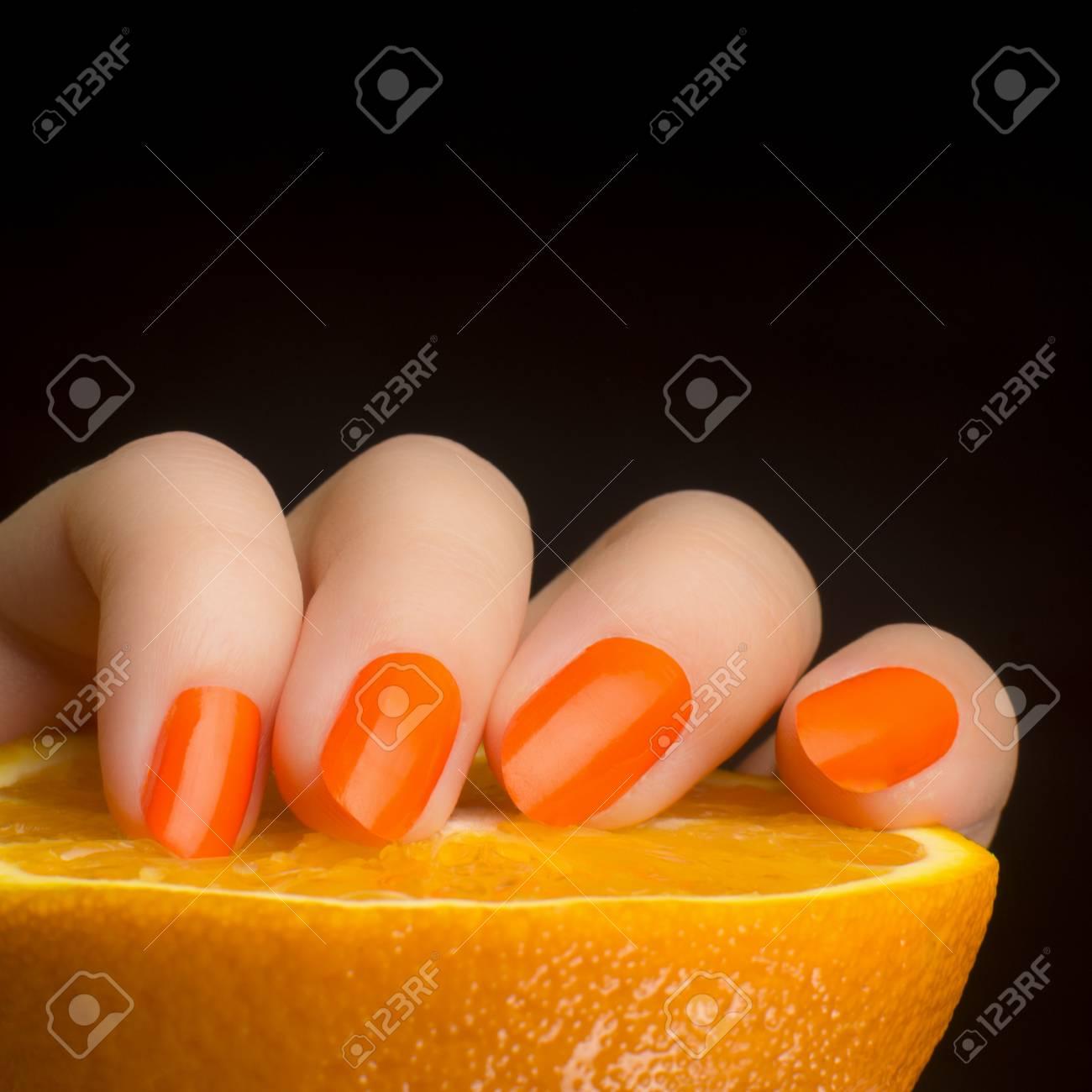 Weibliche Hand Mit Orange Nägel Mit Orange Frucht Auf Schwarzem ...