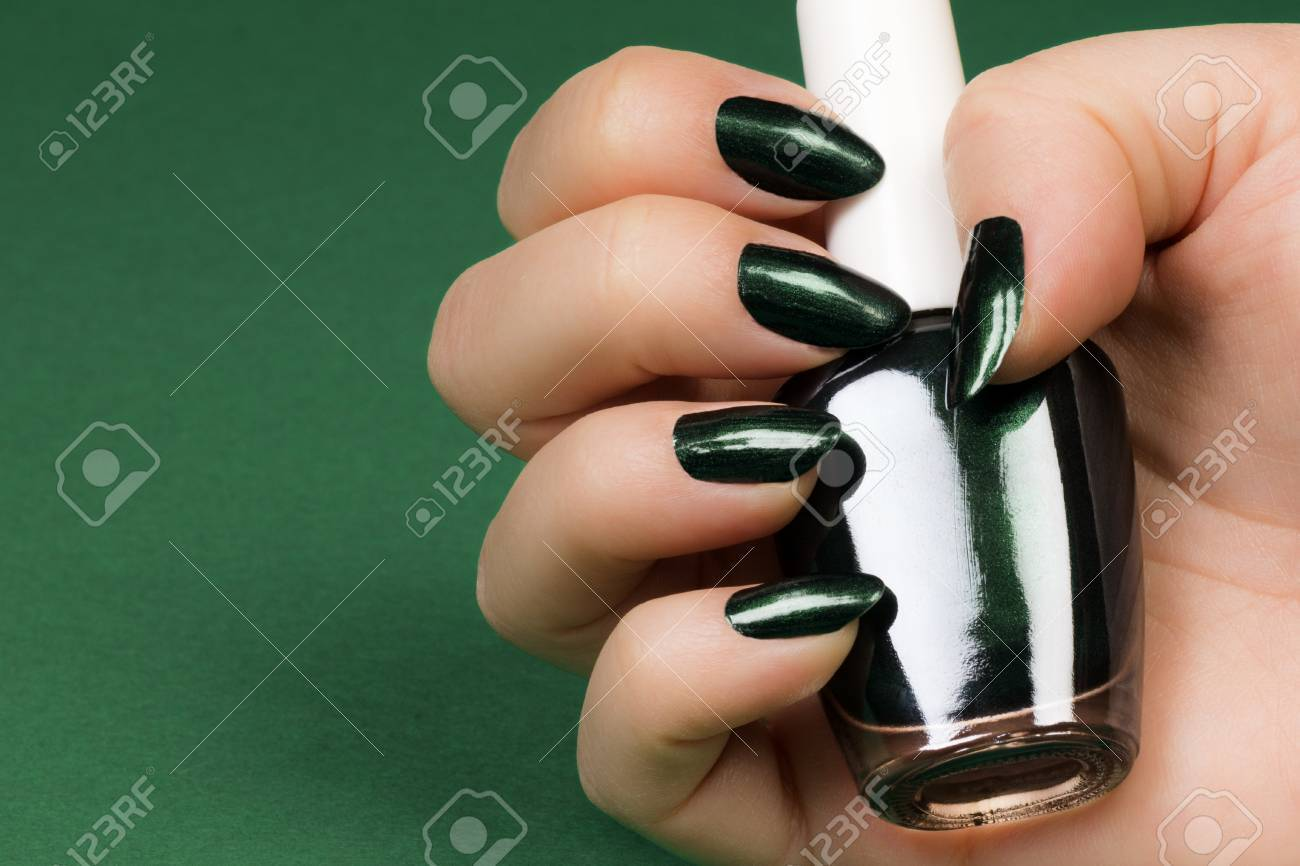 Female Hand With Dark Green Nails Is Holding Dark Green Nail.. Stock ...