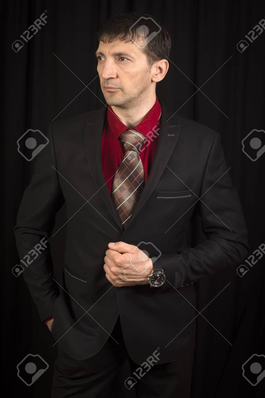 El modelo de moda está en elegante traje negro con corbata sobre fondo negro.  Foto a2b40225f66