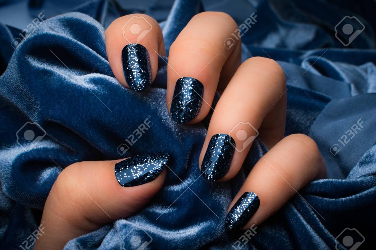 Die Weibliche Hand Mit Dunkelblauen Glittered Nägeln Hält Blaues ...