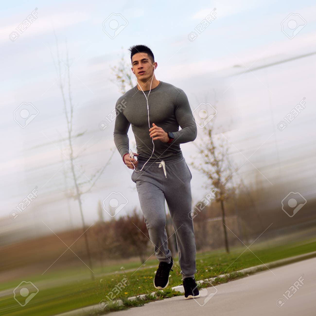 feddf1e7ff44 Stock Photo - The sporty handsome man is jogging and running outdoors as  recreation or sport training with earphones and phone.