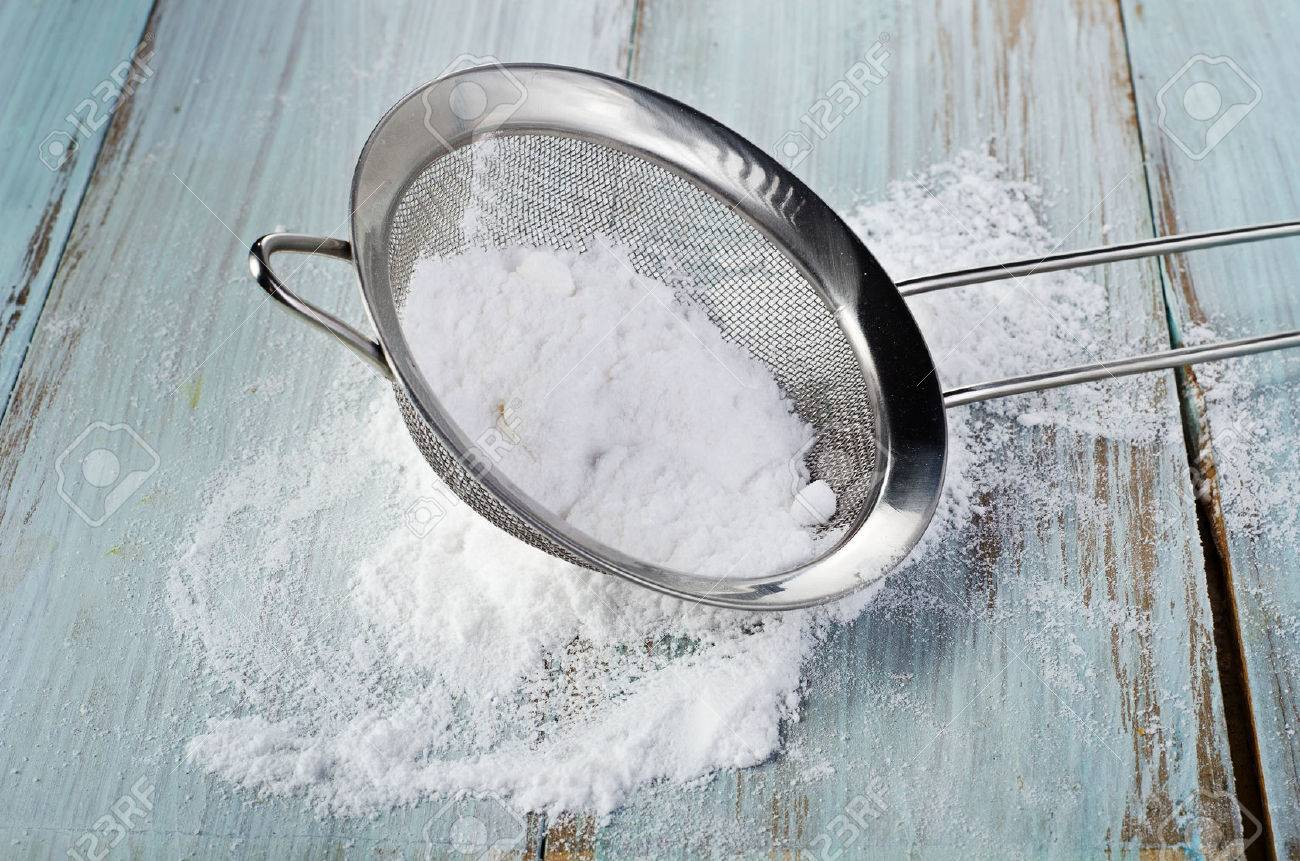 Powdered sugar in a metal sieve on wooden table. Selective focus - 23998673
