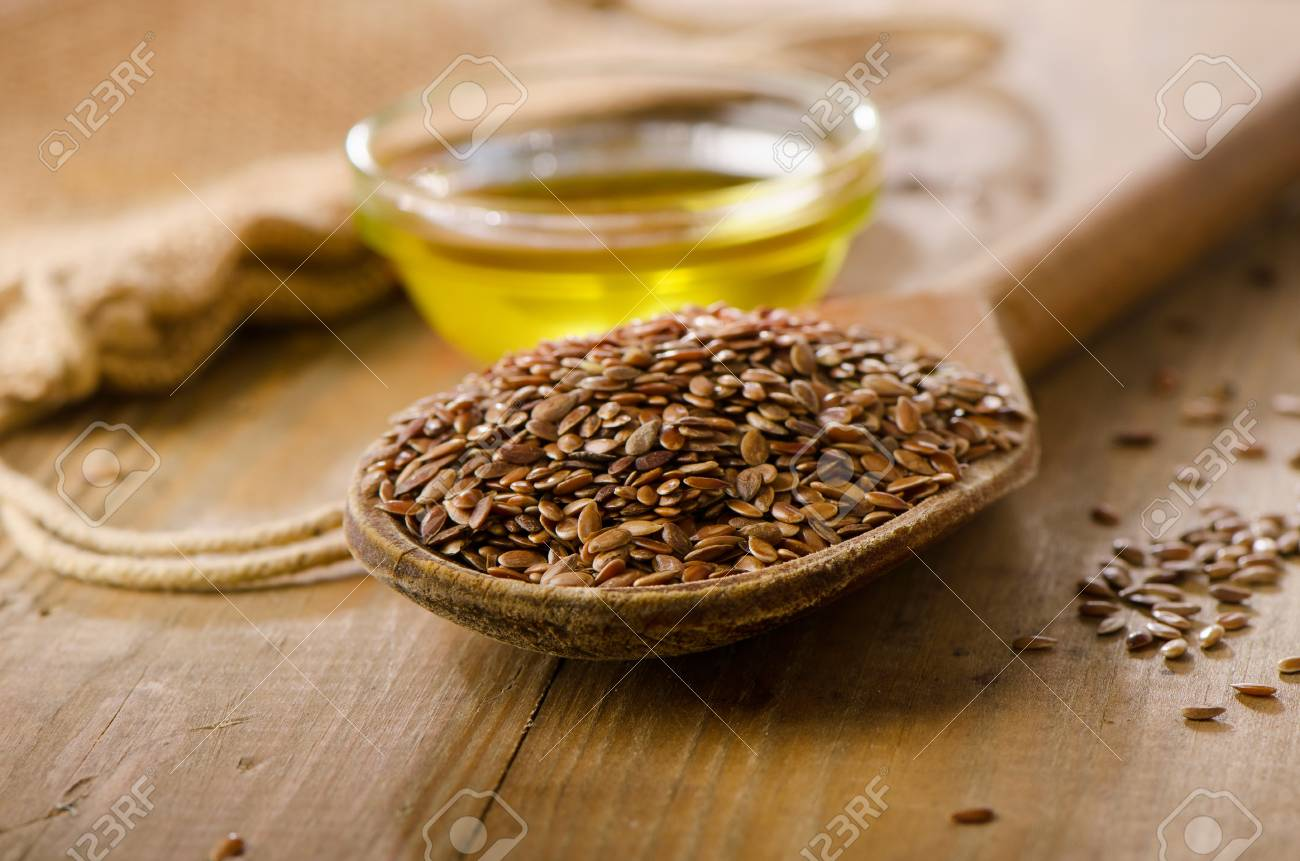 Brown Flax Seeds On A Spoon And Flaxseed Oil On A Wooden Table
