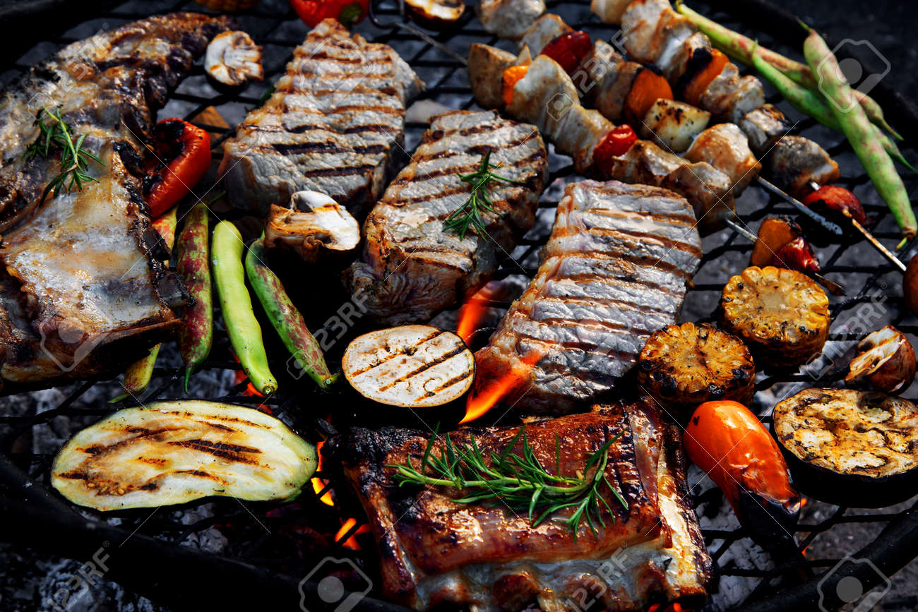 Grilled meat and vegetables on barbecue kettle. Outdoor food concept. Top view - 169654779