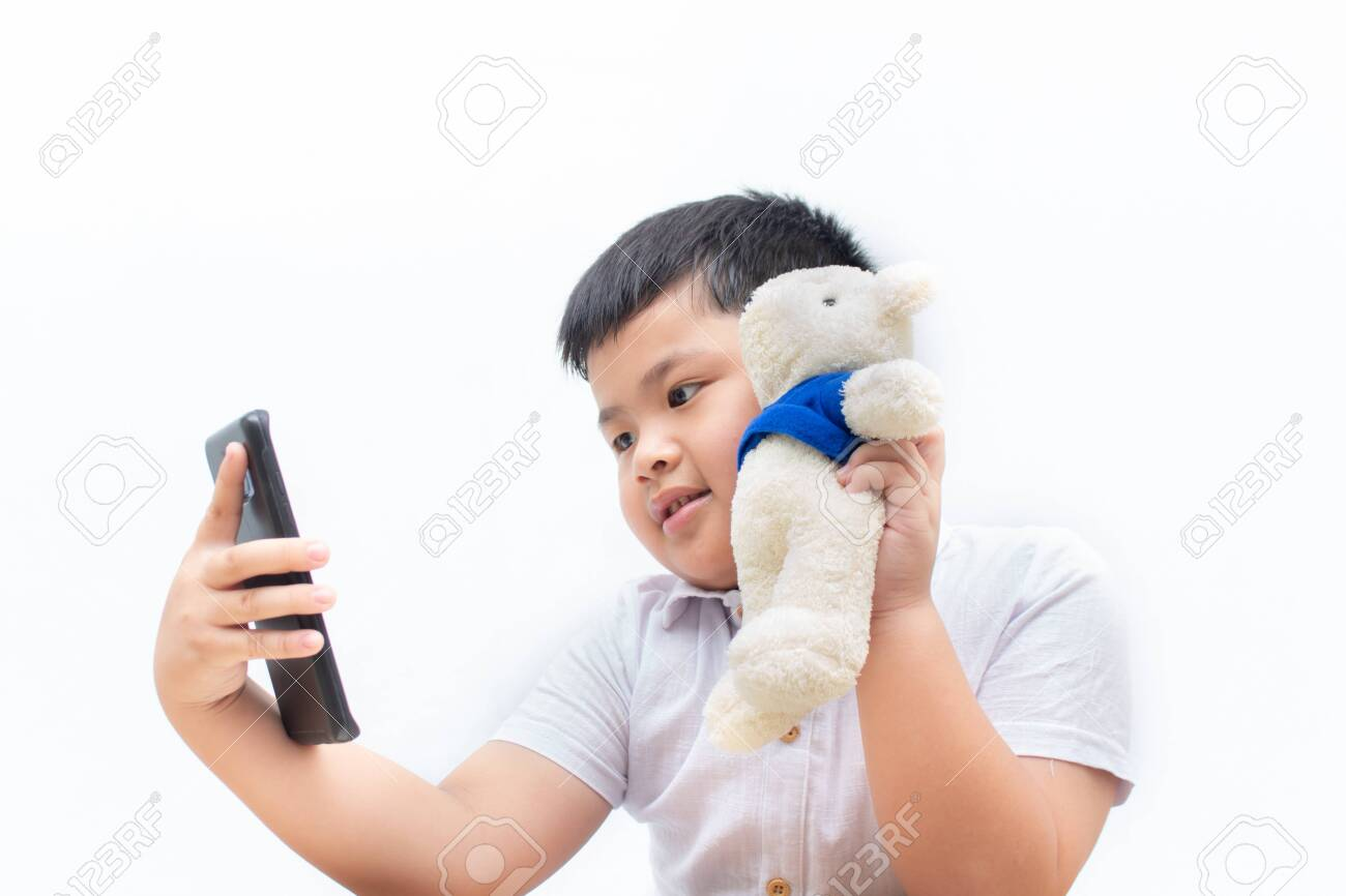 134719476 cute a little boy selfie with bear on white background boy holding a black smart phone