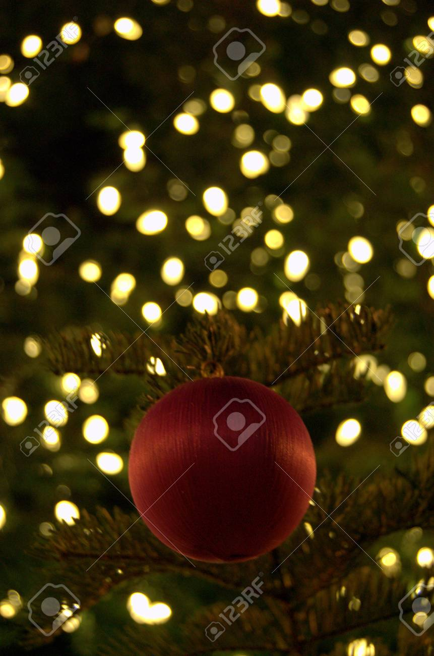 red christmas ball ornament in lighted christmas tree stock photo 34220948