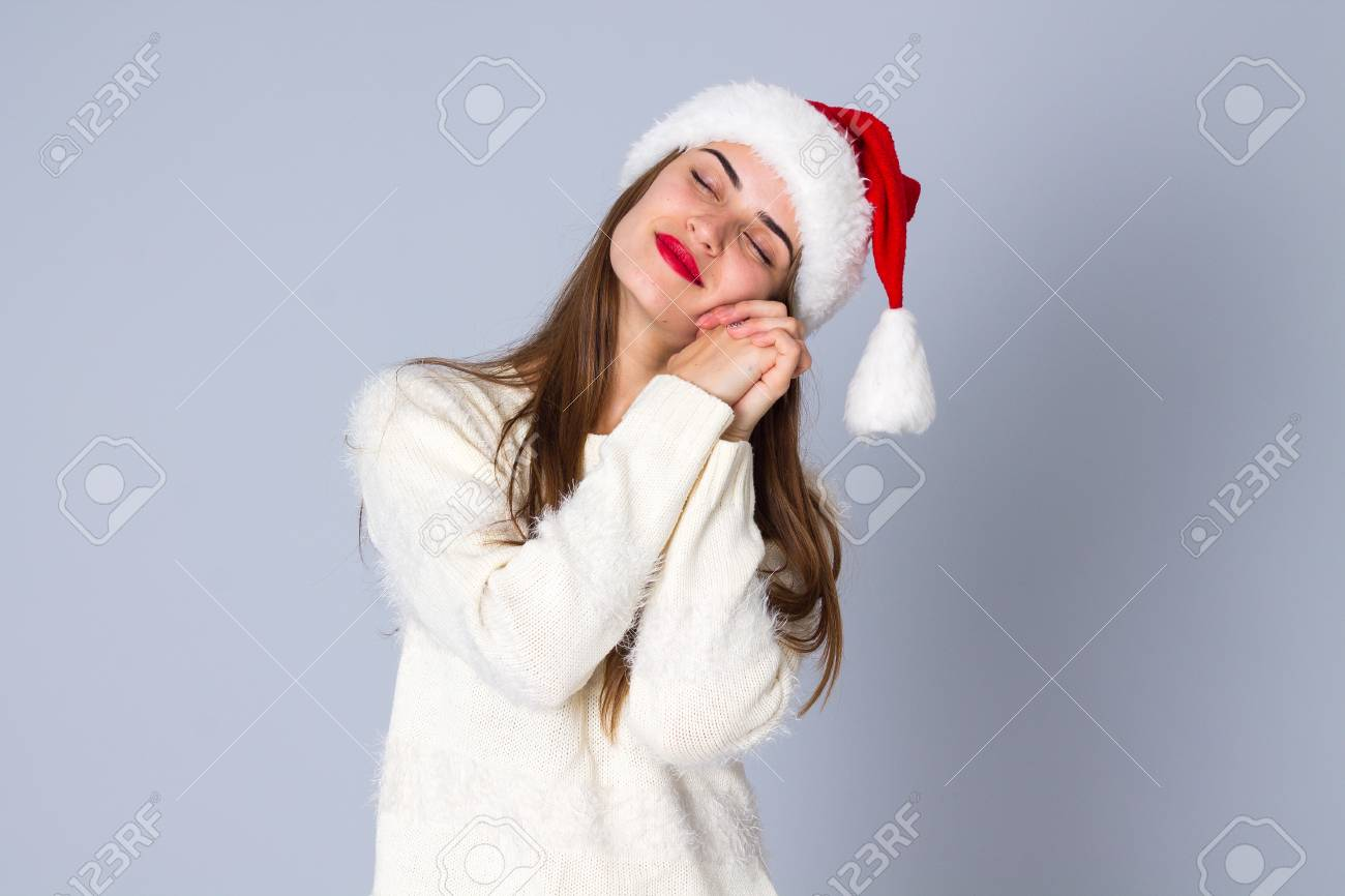 f072111f379a7 Nice young woman in white sweater with long hair and red christmas hat  dreaming on grey