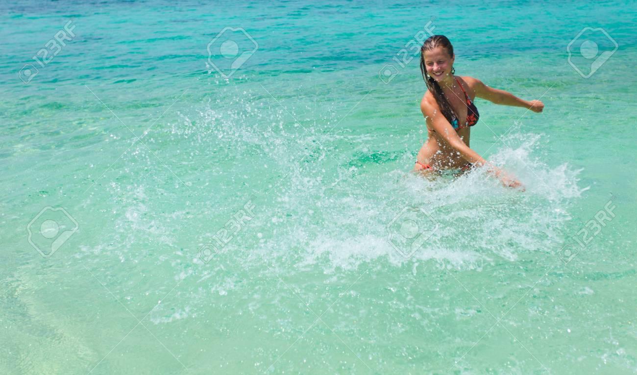 41141736b Foto de archivo - Joven y bella mujer en traje de baño que salpica en el  agua en la orilla del mar
