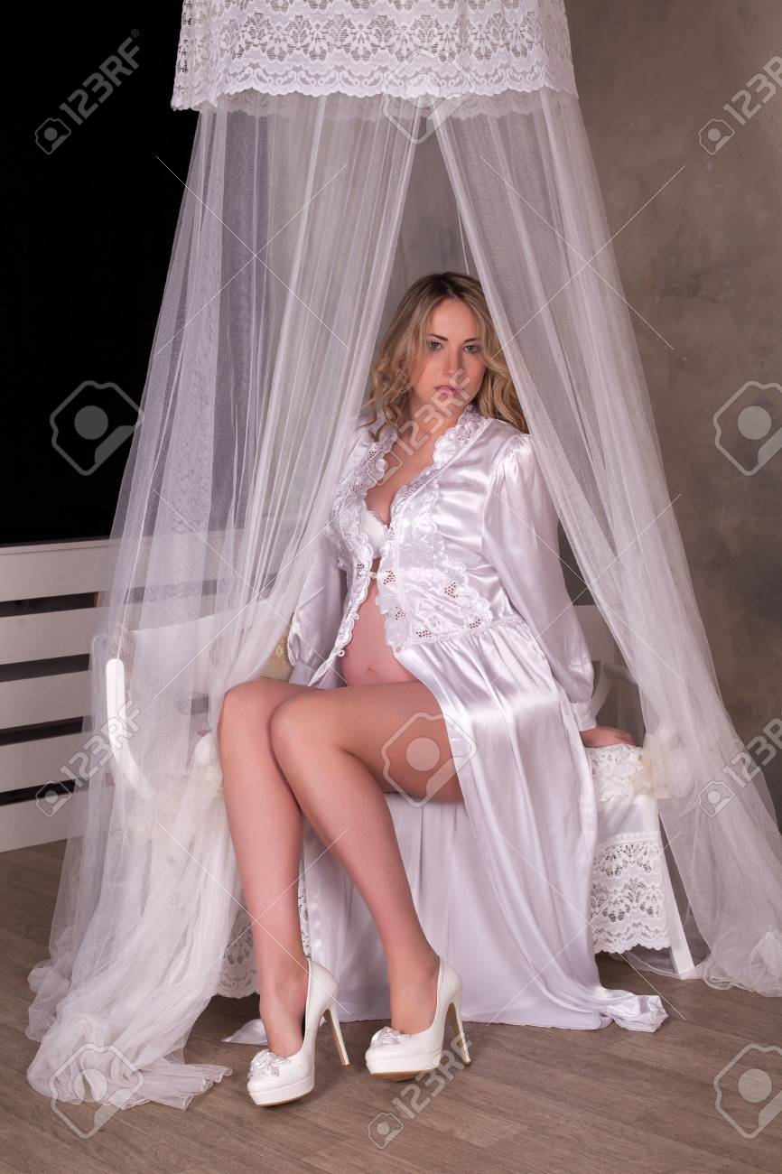 Pretty Pregnant Woman In White Silk Dressing Gown And White Shoes