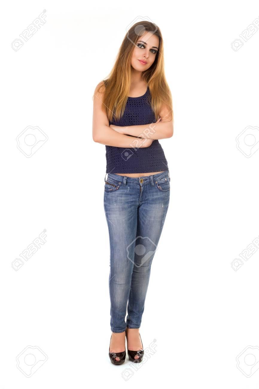 La mujer en jeans ajustados está con los brazos cruzados sobre el fondo blanco.