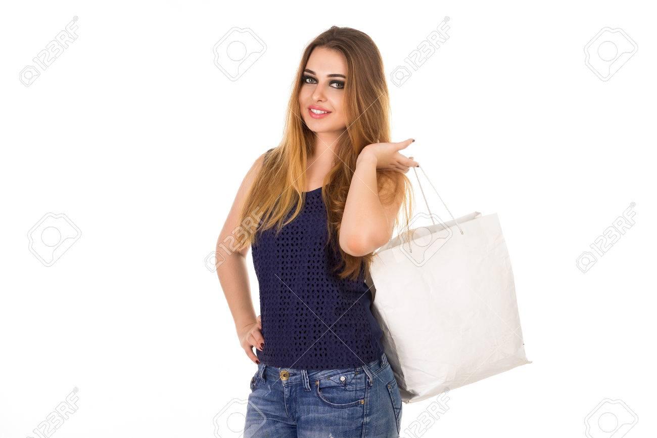 Mujer sonriente en jeans ajustados azules con el bolso blanco está de pie en el fondo blanco.