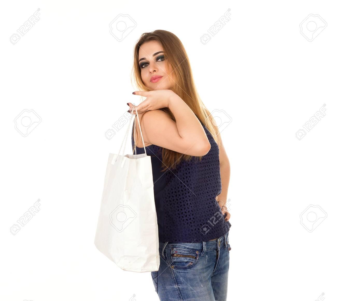 La mujer intight tejanos con el bolso blanco está de pie en el fondo blanco.