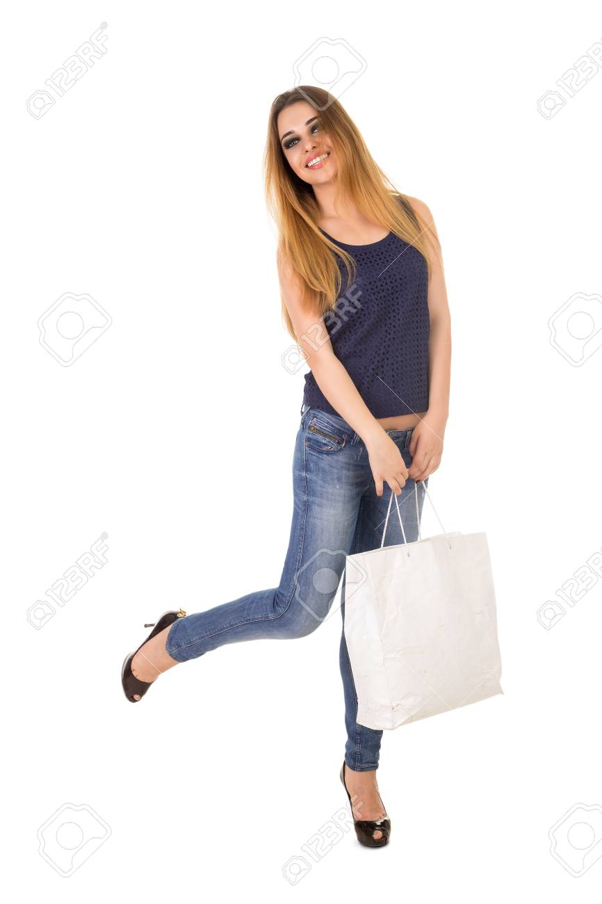 La mujer en jeans ajustados azules con el bolso blanco en sus manos está de pie sobre los talones en el fondo blanco.