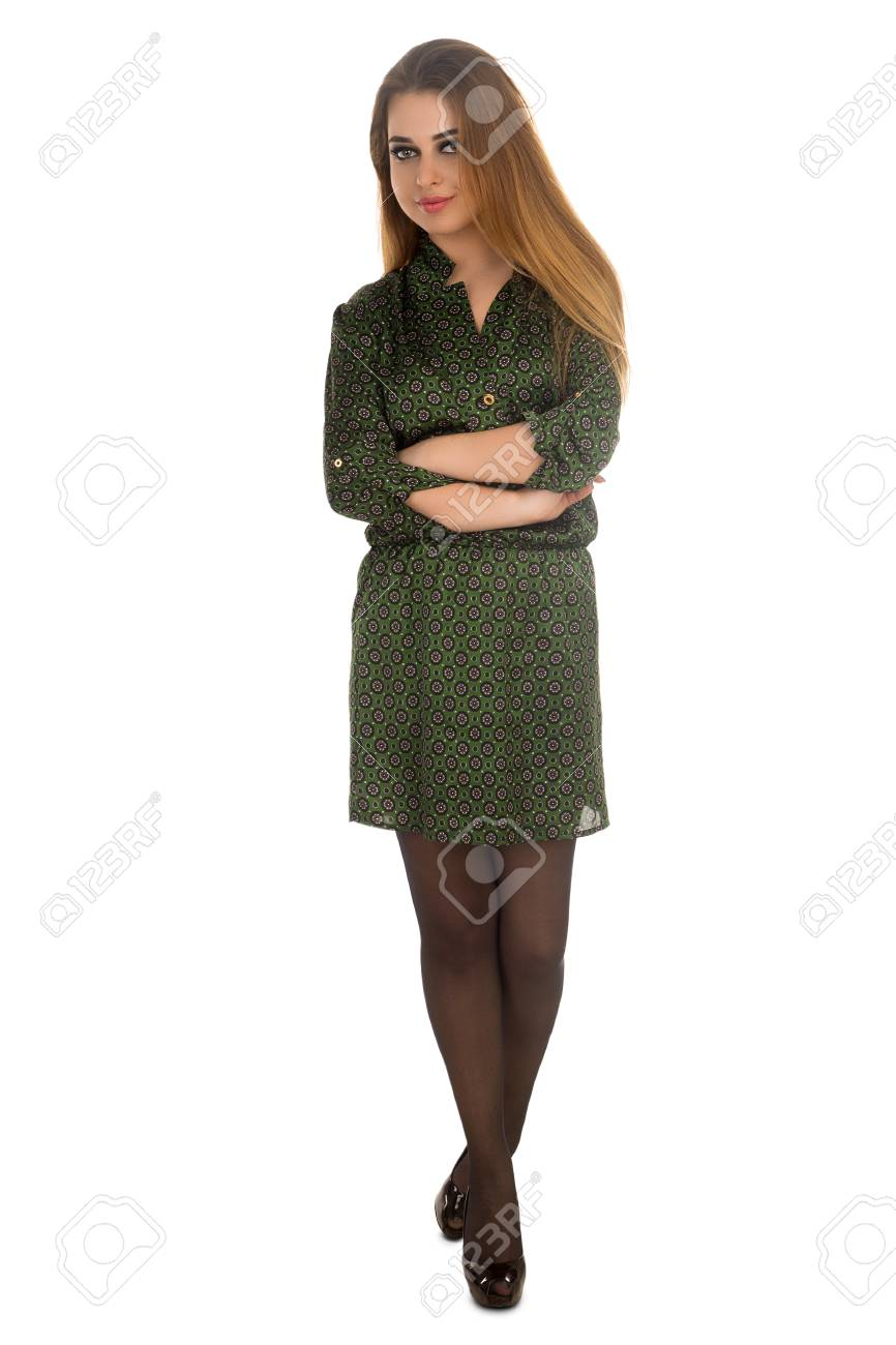 69db2d3a684 Stock Photo - The woman in black tights and green dress with a pattern is  standing with folded arms on the white background.